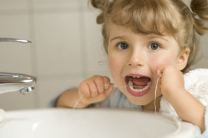 Cute girl cleaning teeth by floss in bathroom